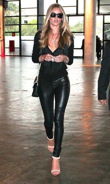Modelo veste calça de couro preta, blusa na mesma cor meia manga e sandalia branca.