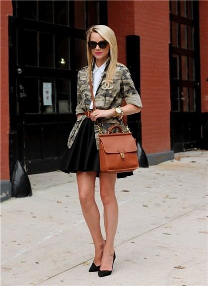 modelo veste saia preta de preguinhas, sapato scarpin, camiseta branca, camisa camuflada e bolsa caramelo.