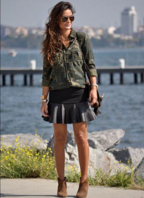 modelo usa saia de couro preta com preguinhas, botinha marrom e camisa camuflada verde.