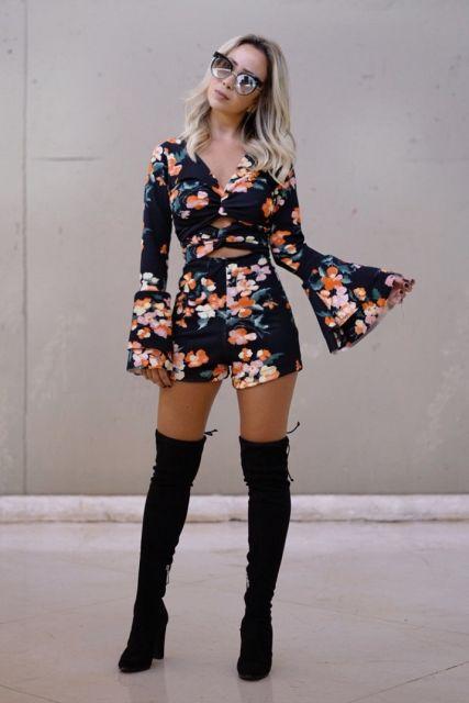 Modelo usa macaquinho estampado preto com detalhes nas cores branco e laranja, com bota cano longo na altura da coxa preta.