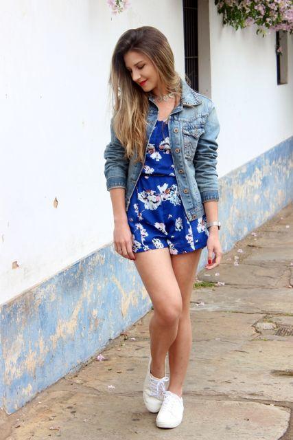Modelo usa macaquinho estampa miudinha floral, na cor azul e branco, com jaquetinha jeans e tenis branco.