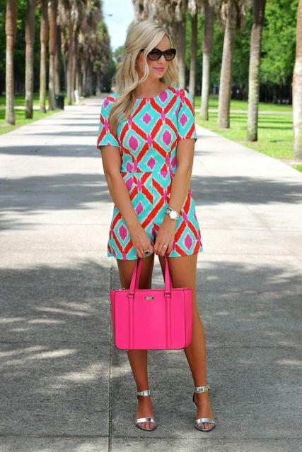 Modelo usa macaquinho estampado de azul claro e vermelho, com bolsa rosa e sandalia branca.