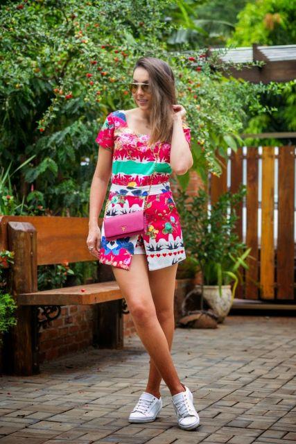 Modelo usa macaquinho estampado em tons, rosa, verde, vermelho, bolsinha pequena cor de rosa e tenis branco.