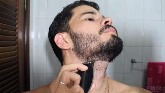 Homem de frente para a câmera raspando sua barba na região do pescoço