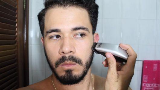 Homem de frente para a câmera passando a máquina de corte na região lateral de sua barba