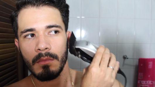 Homem de frente para a câmera passando a máquina de corte em sua barba
