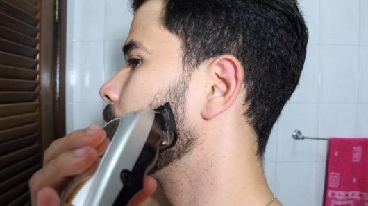 Homem de perfil raspando a região lateral da barba