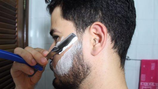 Homem de perfil com creme de barbear em seu rosto passando a gilete na barba