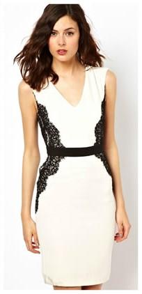 Modelo veste vestido branco com detalhes de renda preta nas laterais.