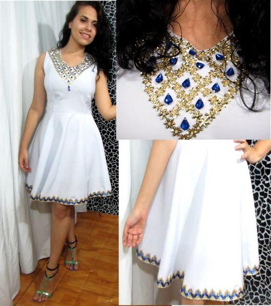 Modelo com vestido branco customizado com pedras.