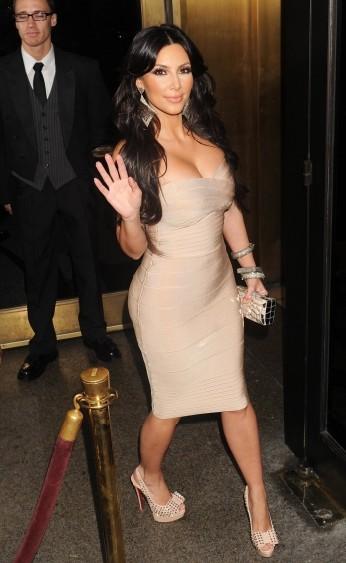 Kim Kardashian usa vestido nude tomara que caia com sapato na mesma cor com laço.