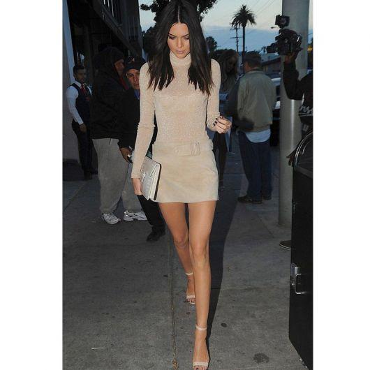 Modelo usa vestido manga longa curto cor nude e sandalia na mesma cor.