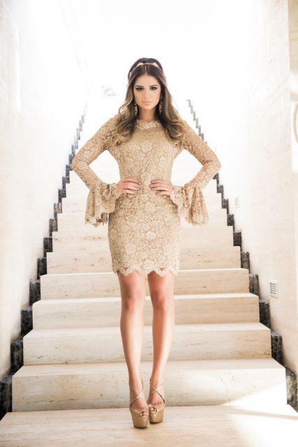 Modelo usa vestido nude colado com manga longa flare e sapato plataforma cor nude.
