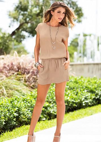 Modelo veste vestido nude liso, com colar dourado e sandália na mesma cor.