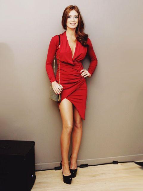 Modelo usa verstido vermelho manga longa, sapato preto plataforma e bolsa de de alça corrente.