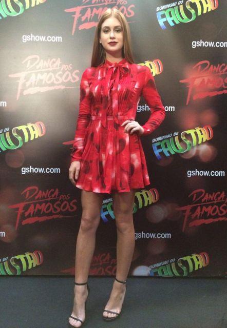 Modelo usa vestido estampado vermelho, manga longa com golinha fechada e sandália preta de tiras finas.