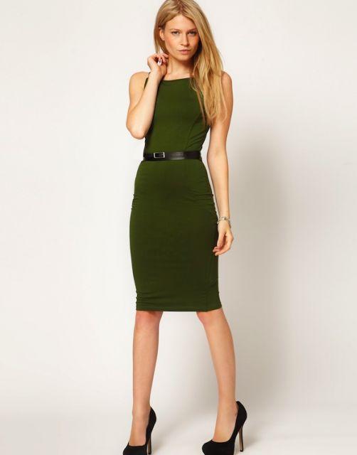 Modelo veste vestido curto midi, verde militar, modelo regata, com cintinho preto e sapato na mesma cor.