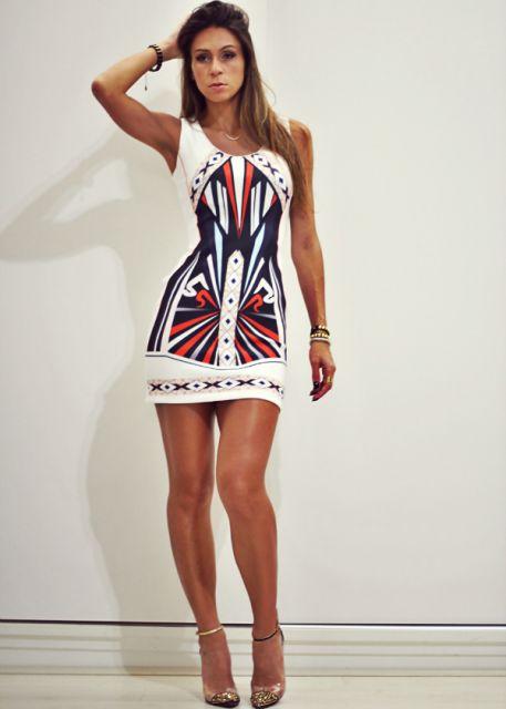 Modelo veste vestido branco com estampa étnica e sandália em tons terrosos.