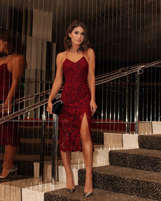 Modelo veste vestido vermelho escuro de alcinhas.,