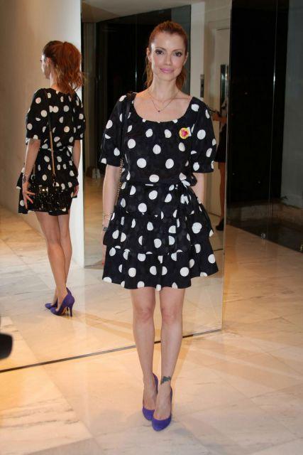 Modelo usa vestido de bolinha preto e branco, com sapato roxo.