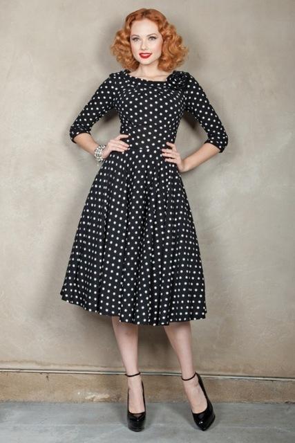58305abcc Modelo veste vestido corte godê,meia manga preto de bolinhas com sapato  preto.