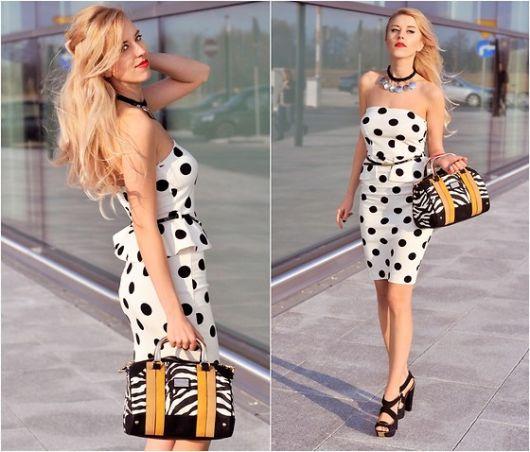 modelo usa vestido branco de bolinha preta com bolsa amarelo marrom e preto e branco, com sandalia preta.