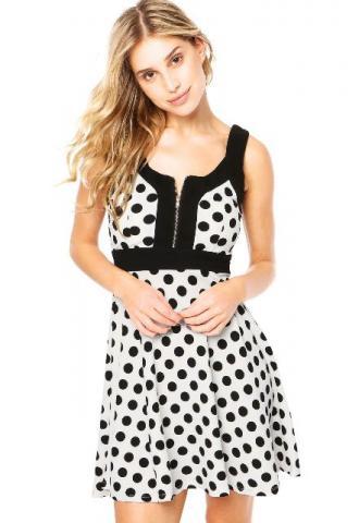 Modelo usa vestido de bolinhas preto e branco com detalhe no decote.