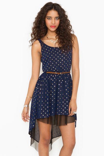 Modelo veste vestido azul escuro, estampa miudinha, com cintinho fininho.