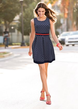 Modelo usa vestido curto azul de bolinhas miudas e sandalia vermalha.
