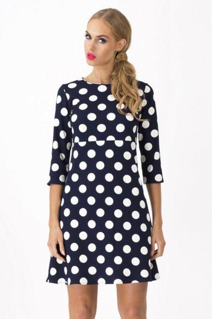 Modelo usa vestido azul com bolas graudas em branco, meia manga.