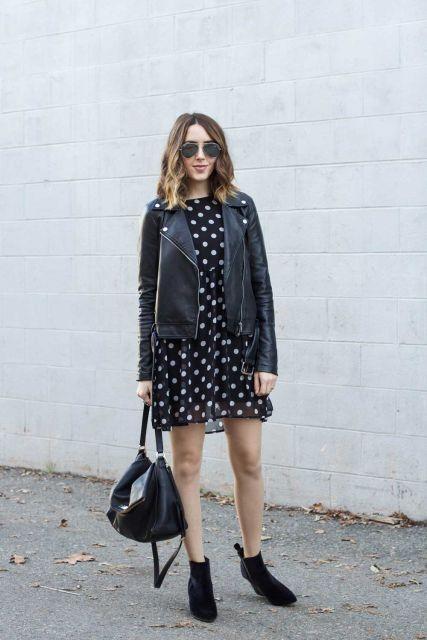 Modelo usa look com botinha preta despojada, jaqueta de couro, bolsa preta de couro e vestido de bolinha preto e branco.
