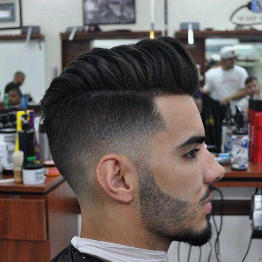 Homem de perfil na barbearia com uma barba bem curta e cabelo arrepiado