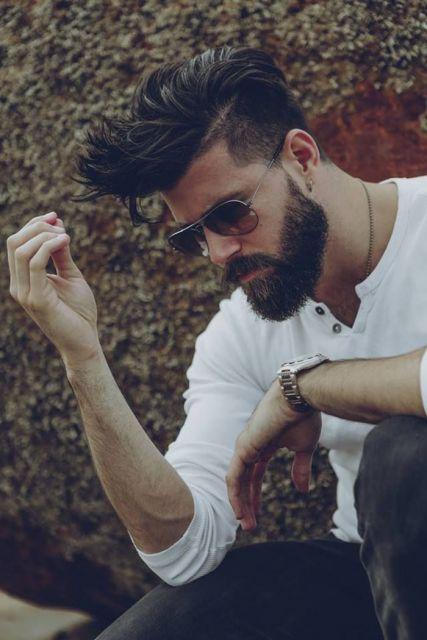 Homem de perfil olhando para baixo, com cabelo arrepiado comprido e barba degradê estilo lenhador