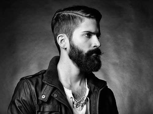 Homem de perfil com cabelo curto nas laterais e barba degradê estilo lenhador