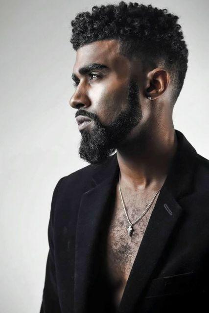 Homem de perfil com a camiseta aberta. Possui uma barba degradê com cavanhaque estendido.