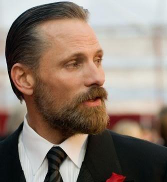 Homem de terno e cabelo jogado para trás olhando para o lado. Possui uma barba degradê com cavanhaque estendido.