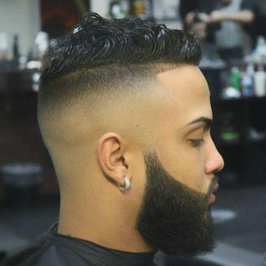 Homem de perfil com brinco na orelha e cabelo arrepiado. Possui uma barba degradê com cavanhaque estendido.