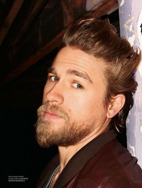 Homem loiro olhando diretamente para a câmera. Possui uma barba degradê com cavanhaque estendido.