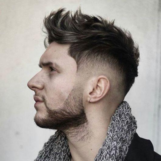Homem de perfil olhando para cima. Possui cabelo liso arrepiado e barba bem feita com degradê na lateral.