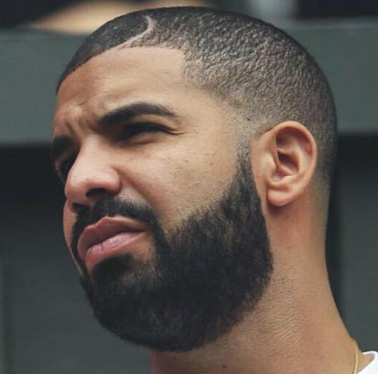 Rapper Drake olhando para o lado com cabeça raspada e barba degradê