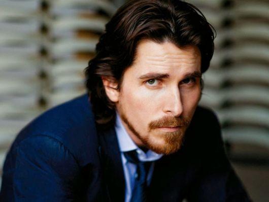 Ator Christian Bale olhando diretamente para a câmera. Está usando um terno azul, cabelo comprido e barba degradê.