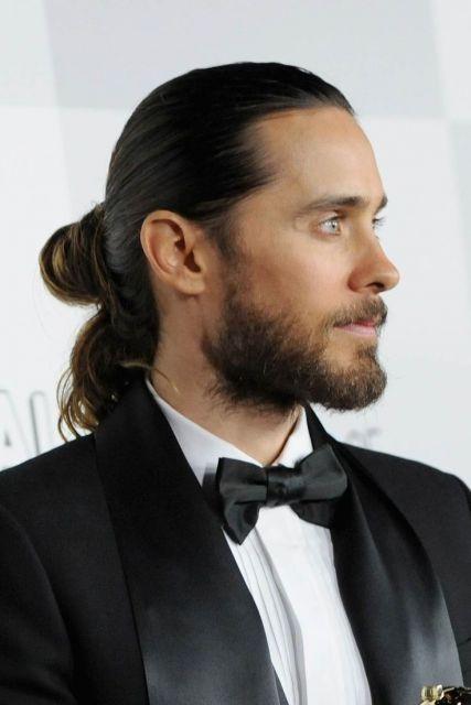 Ator e cantor Jared Leto de perfil com cabelo longo e barba degradê.