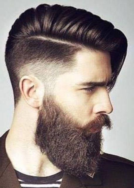Homem de perfil com barba degradê estilo lenhador e cabelo grande jogado para o lado