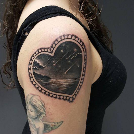 Tatuagem de um coração com uma paisagem dentro, onde há montanhas, o mar e o céu estrelado