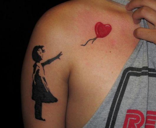 Tatuagem de um balão em forma de coração voando para longe de uma garota que olha para ele