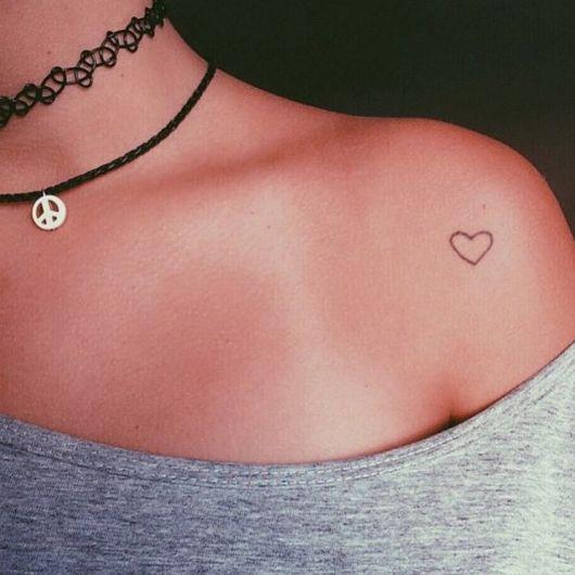 Tatuagem do contorno de uma coração no ombro de uma mulher