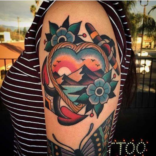 Tatuagem colorida de um coração no ombro. Seu interior possui a paisagem de uma montanha e ele é envolto por uma âncora e duas flores
