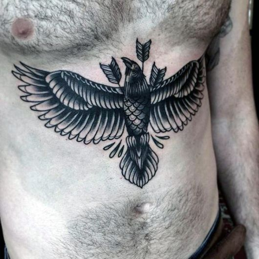 Tatuagem de corvo em barriga masculina