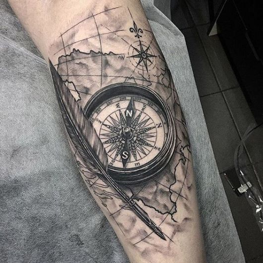 Tatuagem em um braço de uma bússola ao lado de uma pena, ambos em cima de um mapa