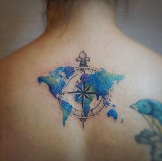 Tatuagem nas costas de uma mulher do mapa mundi pintado de azul em aquarela com um bússola transparente na frente
